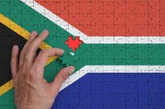 A bandeira de África do Sul é descrita em um enigma, que a mão do ` s do homem termine para dobrar fotografia de stock