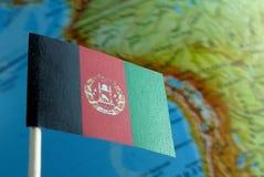 Bandeira de Afeganistão com um mapa do globo como um fundo Foto de Stock