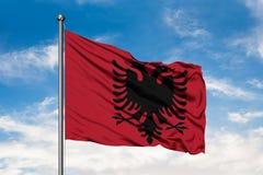 Bandeira de Albânia que acena no vento contra o céu azul nebuloso branco imagens de stock royalty free