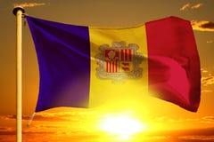 Bandeira de Andorra que tece no por do sol alaranjado bonito com fundo das nuvens ilustração do vetor