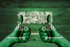 Bandeira de Arábia Saudita pintada nos polegares fêmeas das mãos acima imagens de stock royalty free