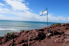 Bandeira de Argentina em uma costa de mar Imagens de Stock Royalty Free