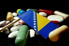 A bandeira de Bósnia e de Herzegovina com lote de comprimidos médicos isolou o Foto de Stock Royalty Free