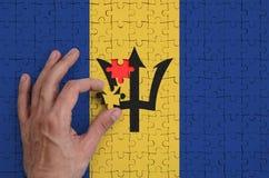 A bandeira de Barbados é descrita em um enigma, que a mão do ` s do homem termine para dobrar imagens de stock