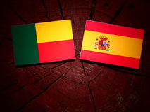 Bandeira de Benin com bandeira espanhola em um coto de árvore foto de stock