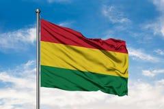 Bandeira de Bolívia que acena no vento contra o céu azul nebuloso branco Bandeira boliviana foto de stock