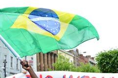 Bandeira de Brasil que está sendo guardado em um protesto Imagens de Stock Royalty Free