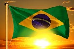 Bandeira de Brasil que tece no por do sol alaranjado bonito com fundo das nuvens foto de stock