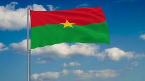 Bandeira de Burkina Faso contra o fundo das nuvens que flutuam no céu azul ilustração stock