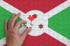 A bandeira de Burundi é descrita em um enigma, que a mão do ` s do homem termine para dobrar fotos de stock