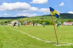 A bandeira de canto retro no primeiro plano do campo de futebol amador, no fundo obscuro é jogadores de futebol que lutam pela bo imagem de stock