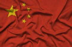 A bandeira de China é descrita em uma tela de pano dos esportes com muitas dobras Bandeira da equipe de esporte imagens de stock royalty free