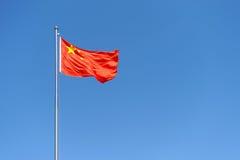 Bandeira de China de encontro ao céu azul desobstruído Imagem de Stock