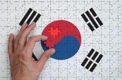 A bandeira de Coreia do Sul é descrita em um enigma, que a mão do ` s do homem termine para dobrar foto de stock royalty free