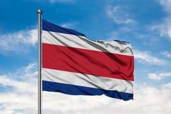 Bandeira de Costa Rica que acena no vento contra o céu azul nebuloso branco Costa Rican Flag fotos de stock