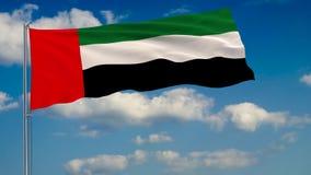 Bandeira de Emiratos Árabes Unidos contra o fundo das nuvens que flutuam no céu azul ilustração do vetor
