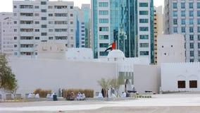 A bandeira de Emiratos Árabes Unidos que acena em torno de uma construção árabe do estilo do vintage, o museu de Qasr Al Hosn em