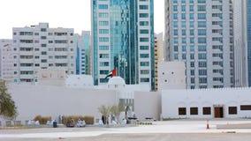 A bandeira de Emiratos ?rabes Unidos que acena em torno de uma constru??o ?rabe do estilo do vintage, o museu de Qasr Al Hosn em