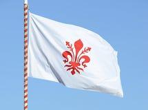 Bandeira de Florença com o lírio vermelho que acena no céu foto de stock