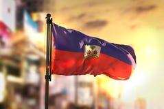 Bandeira de Haiti contra o fundo borrado cidade no luminoso do nascer do sol foto de stock