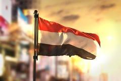 Bandeira de Iémen contra o fundo borrado cidade no luminoso do nascer do sol Foto de Stock Royalty Free