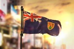 Bandeira de Ilhas Turcos e Caicos contra o fundo borrado cidade em Imagem de Stock Royalty Free