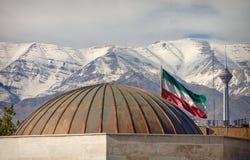 Bandeira de Irã e Milad Tower na frente das montanhas cobertos de neve de Alborz Foto de Stock Royalty Free