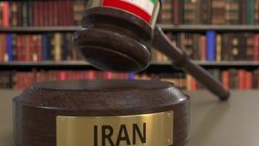 Bandeira de Irã no martelo de queda dos juizes no tribunal Justiça ou a jurisdição nacional relacionaram a animação 3D conceptual video estoque