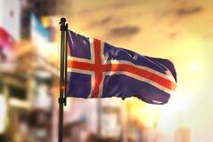 Bandeira de Islândia contra o fundo borrado cidade no nascer do sol Backligh fotografia de stock royalty free