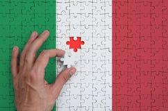 A bandeira de Itália é descrita em um enigma, que a mão do ` s do homem termine para dobrar fotos de stock