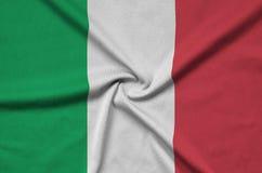 A bandeira de Itália é descrita em uma tela de pano dos esportes com muitas dobras Bandeira da equipe de esporte imagens de stock royalty free