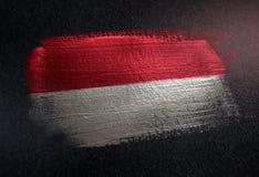Bandeira de Mônaco feita da pintura metálica da escova na parede da obscuridade do Grunge foto de stock royalty free