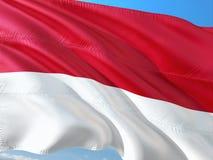 Bandeira de M?naco que acena no vento contra o c?u azul profundo Tela de alta qualidade imagem de stock royalty free