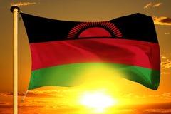 Bandeira de Malawi que tece no por do sol alaranjado bonito com fundo das nuvens fotografia de stock