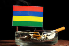 Bandeira de Maurícias com o cigarro ardente no cinzeiro isolado no preto Foto de Stock