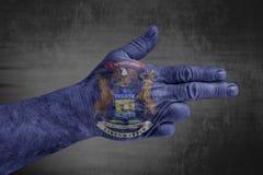 A bandeira de Michigan do estado de E.U. pintou na mão masculina como uma arma fotografia de stock royalty free