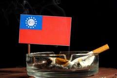 Bandeira de Myanmar com o cigarro ardente no cinzeiro isolado no preto Imagem de Stock Royalty Free
