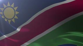 Bandeira de Namíbia que acena no mastro de bandeira no vento, símbolo nacional da liberdade ilustração do vetor
