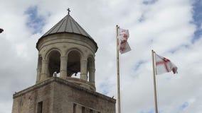 Bandeira de Natioal de Geórgia na frente da catedral de Svetitskhoveli 120fps vídeos de arquivo