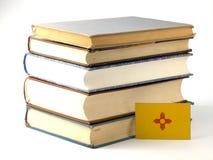 Bandeira de New mexico com a pilha dos livros no fundo branco foto de stock royalty free