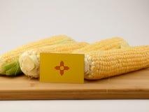 Bandeira de New mexico em um painel de madeira com o milho isolado em um branco imagem de stock