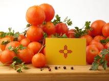 Bandeira de New mexico em um painel de madeira com os tomates isolados em um wh fotos de stock royalty free