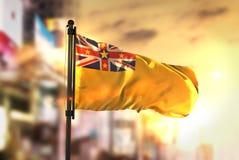 Bandeira de Niue contra o fundo borrado cidade no luminoso do nascer do sol Imagem de Stock Royalty Free
