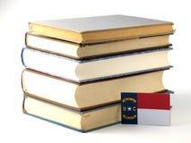 Bandeira de North Carolina com a pilha dos livros isolados no backgro branco Fotografia de Stock Royalty Free