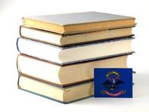 Bandeira de North Dakota com a pilha dos livros isolados no backgroun branco Imagens de Stock