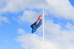 Bandeira de Nova Zelândia contra nuvens brancas bonitas no céu azul Fotos de Stock Royalty Free