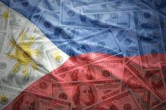 Bandeira de ondulação de Filipinas em um fundo americano do dinheiro do dólar Fotos de Stock Royalty Free