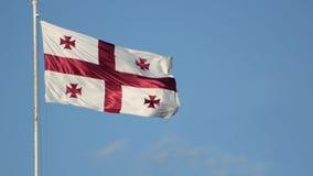 Bandeira de ondulação de Geórgia em um mastro de bandeira contra um céu azul vídeos de arquivo