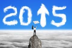Bandeira de ondulação do homem de negócios no pico de montanha com o céu de 2015 nuvens Fotografia de Stock