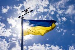 Bandeira de ondulação de Ucrânia contra o céu azul na frente do sol imagens de stock royalty free